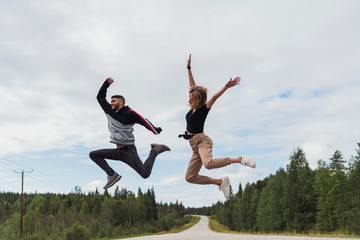 Finland, Lapland, exuberant young couple jumping in rural landscape