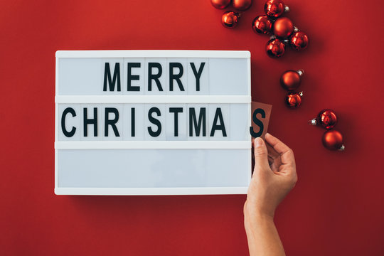 Woman's hands adding letter at 'Merry Christmas' sign