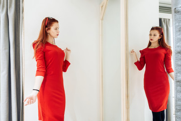 Beautiful young girl trying on a red dress in the store. Pretty woman posing near the whim.