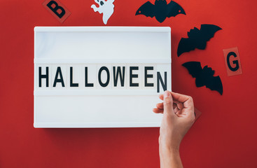 Woman's hands adding letter at 'Halloween' sign