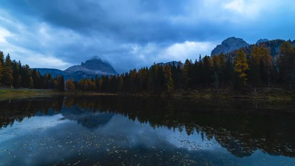 Wall Mural - Sunrise time-lapse shot of autumn landscape of Antorno lake with famous Dolomites mountain peak of Tre Cime di Lavaredo in background in Italian Dolomites.