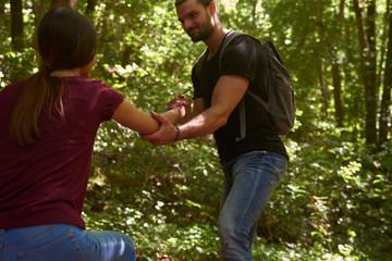 Spain, Canary Islands, La Palma, man helping girlfriend walking up a forest