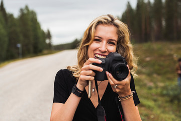 Finland, Lapland, portrait of happy young woman holding camera at country road