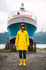 Portrait of young man in yellow raincoat standing in front of ship
