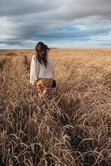 Back view of young woman walking in corn field