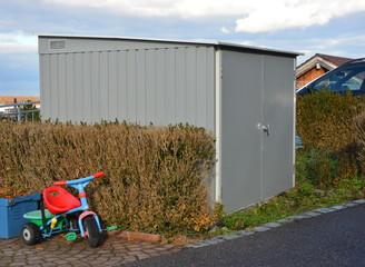 Kombination von Abfall-Sammelbehälter-Einhausung und Geräteunterstand aus Edelstahl vor Mehrfamilien-Wohnhäusern im Neubaugebiet