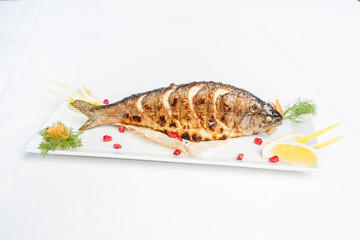 Baked fish on a plate on a white background