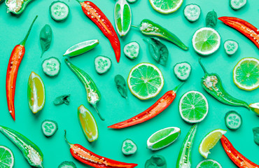 Above view at cutted Chili pepper and basil with cytrus on green background