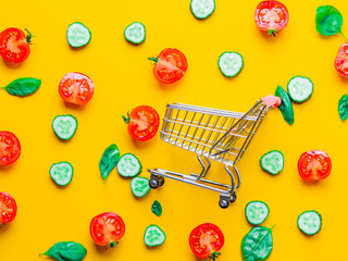Above view at tomatoes, cucumbers and basil with shopping cart on yellow background