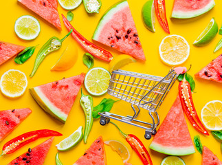 Above view at Watermelon and Chili pepper with lemons near shopping cart on yellow background