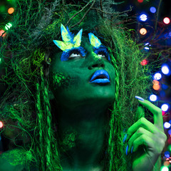 Mystic green dryad in UV fluor black light with Glowing trees on background