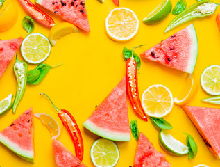 Above view at Watermelon and Chili pepper with lemons on yellow background