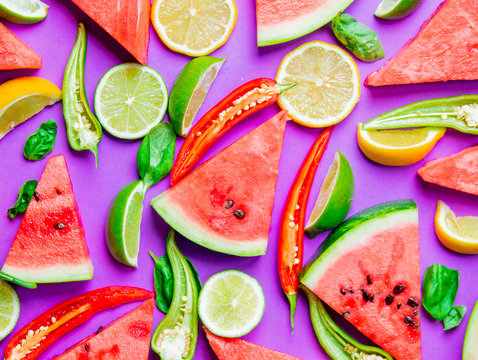 Above view at Watermelon and Chili pepper with lemons on purple background