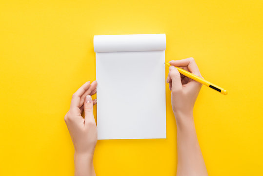 partial view person holding pen over blank notebook on yellow background