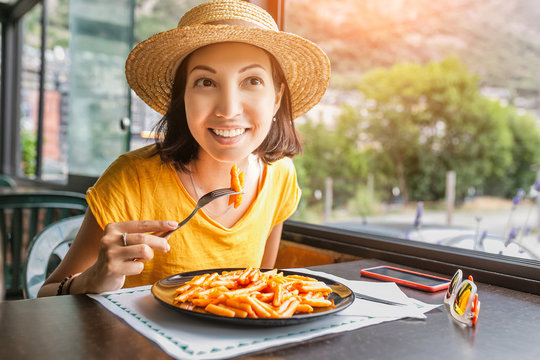 Happy smiling woman in eating pasta in restaurant