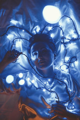 Deurstickers Grandfailure overhead view of woman lying on bed with christmas lights around