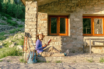 Woman hiker with book or map planning next trip, near the building of a hiking shelter in mountains