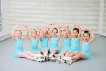 Group of cute little ballet dancers looking at camera at dance school class.