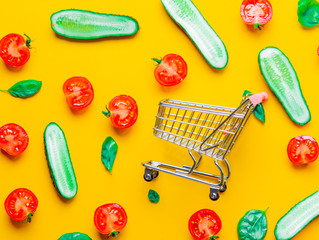 Above view at tomatoes and cucumbers with shopping cart on yellow background