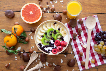 Healthy fresh natural breakfast with yoghurt, fruits, juice and nuts on wood table. Top view