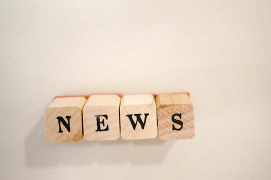 """Holzbuchstaben auf weißem Hintergrund """"NEWS"""""""