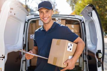 Delivery man standing in front of his van Fototapete