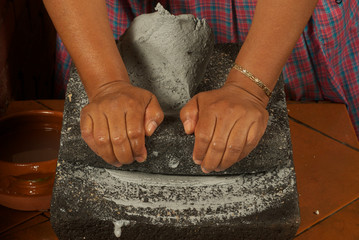 amasando en metate masa de maiz azul para tortillas