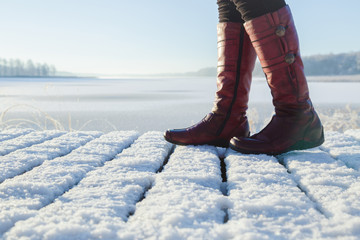 Red, leather, woman boots walking on white snowy boardwalk at frozen lake. Enjoying stroll in early, chilly, sunny morning. Footwear for daily walking in winter season. Closeup. Side view.