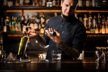 Bartender holding a bottle and pouring an alcoholic drink a cocktail from the steel jigger