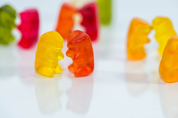 Sweet, delicious gummy bears in small groups, dancing, talking party conceptual image on white shiny surface.