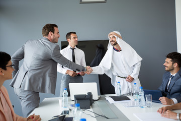 Arabian partner handshake with businessman.