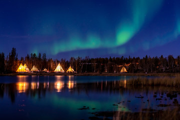 Photo sur Toile Aurore polaire Greenish Aurora Borealis over illuminated Tipi near a lake, Yellow Knife,