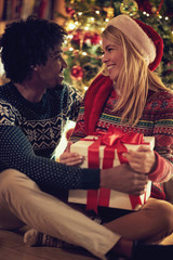 Cheerful man and woman exchanging Christmas presents .