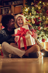Happy male and female exchanging Christmas presents .