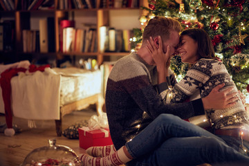 Cheerful man and woman with gift enjoying together on Christmas eve.