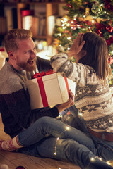 romantic surprise holiday – Cheerful man and woman with gift enjoying together on Christmas eve.