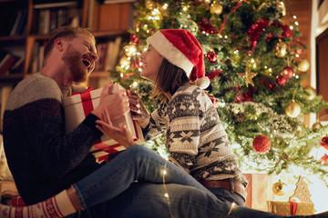 Smiling Christmas couple enjoying in the holidays