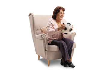 Cheerful elderly woman sitting in an armchair with soccer ball