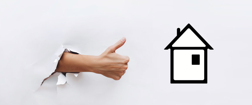 A hand with a raised finger next to the symbol of the house, cottage. The concept of buying an apartment, loan, mortgage, excellent quality of the building company.