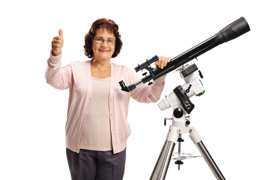 Elderly woman with a telescope looking at the camera and showing thumbs up