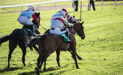Three jockeys and race horses in intense competition for first place