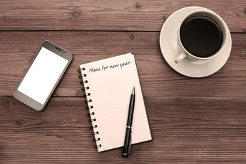 phone, notebook with the inscription Plans for the new year:, ballpoint pen, a Cup of coffee on a wooden background. business plan.