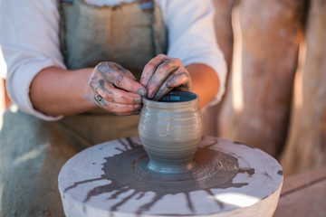 Potter is creating earthenware on potter's wheel.