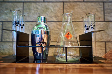 Shaker, flask and test tubes with the symbol of biological hazard, flammable liquid and radiation on a metal rack.
