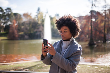 Serious afro woman using her smart phone in the park