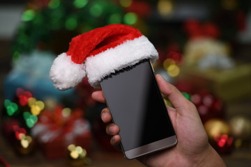Hand holding mobile phone with Santa Claus' hat on top on Christmas background
