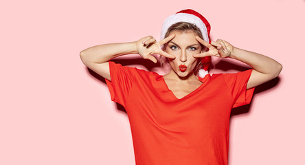 Wall Mural - Portrait of funny young woman fooling around and showing peace sign. Christmas concept. Studio picture of pretty girl wearing santa hat and posing on pink background