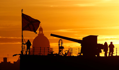 Visitors are seen on the deck of the Cruiser Aurora museum during sunset, with Saint Isaac's Cathedral seen in the background, in St. Petersburg