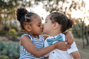 Cute siblings kissing while standing in park during sunset