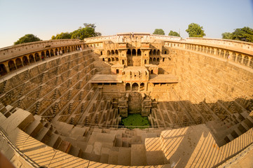 Fisheye shot of the abhaneri stepwell in jaipur rajasthan. Shows the steps, the palace and the green water with all the details of the beautiful stepwell, the surrounding area and the blue sky